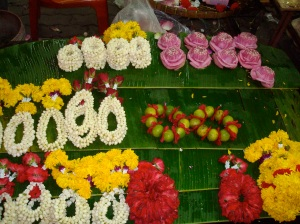 These are handmade flower offerings for sale across the streets from the Hindu temple. Yes, those are lotus flowers in the right rear corner.